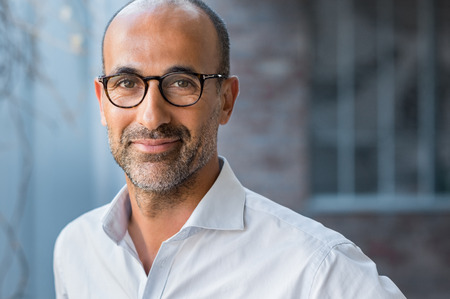 Photo for Portrait of happy mature man wearing spectacles and looking at camera outdoor. Man with beard and glasses feeling confident. Close up face of hispanic business man smiling. - Royalty Free Image