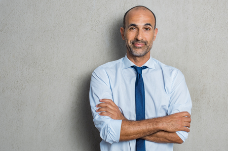 Foto de Portrait of happy smiling mature businessman standing against grey background while looking at camera. Proud senior business man against grey wall with copy space. Executive manager with arms crossed smiling. - Imagen libre de derechos
