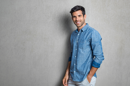 Foto de Happy smiling man leaning against grey wall. Portrait of proud mid man isolated on grey background. Young casual hispanic man against grey wall looking at camera. - Imagen libre de derechos