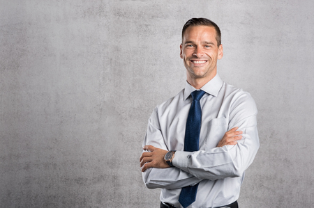 Foto de Happy businessman looking at camera on grey background with copy space. Handsome young business man standing against a grey wall with crossed arms. Successful formal man smiling with copy space. - Imagen libre de derechos