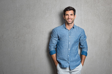 Photo pour Portrait of a handsome young man smiling against grey background with copy space. Smiling latin guy with hands in pocket in blue shirt standing and leaning on wall. Successful hispanic man looking at camera. - image libre de droit