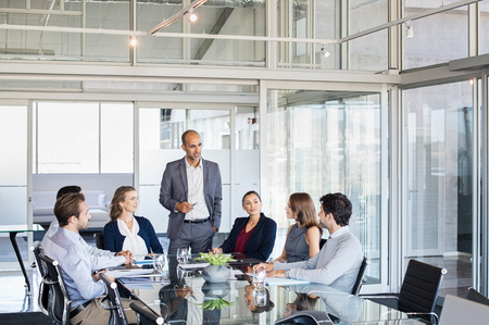 Foto de Human resource manager training people about company and future prospects. Group of businesspeople sitting in meeting room and listening to the speaker. Leader man training his work group in a conference room. - Imagen libre de derechos
