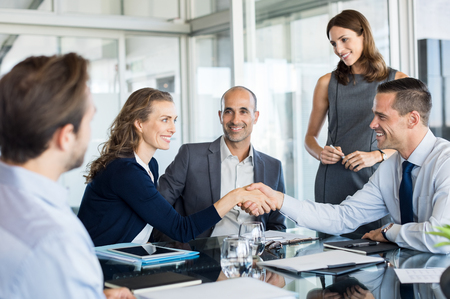 Photo pour Handshake to seal a deal after a meeting. Two successful business people shaking hands in front of their colleagues. Mature businesswoman shaking hands to seal a deal with smiling businessman. - image libre de droit