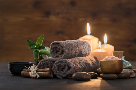 Foto de Brown towels with bamboo and candles for relax spa massage and body treatment. Beautiful composition with candles, spa stones and salt on wooden background. Spa and wellness setting ready for beauty treatment. - Imagen libre de derechos