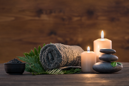 Foto de Brown towel on green fern with candles and black hot stone on wooden background. Hot stone massage setting lit by candles. Hot stone therapy for one person with candle light. Beauty spa treatment and relax concept. - Imagen libre de derechos
