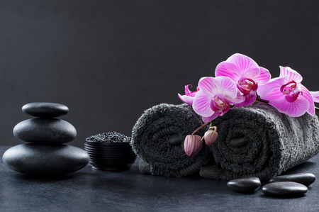 Foto de Black spa setting with grey towels, hot stones and beautiful orchids. Spa and wellness background with stack of hot stones with pink flowers on blackboard. Luxury spa composition and relax concept. - Imagen libre de derechos