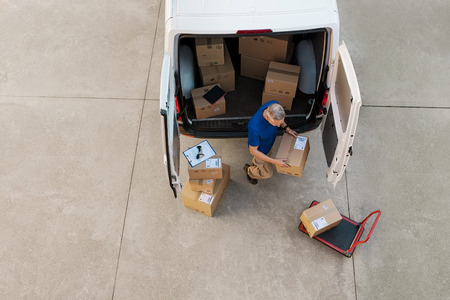 Photo pour Delivery man holding cardboard box and unloading parcel for delivery. Top view of courier unloading parcels from van. High angle view of man removing packages for the delivery. - image libre de droit
