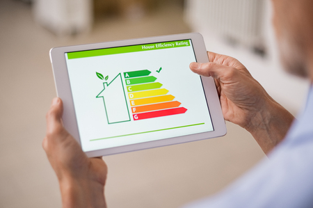 Foto de Hand holding digital tablet and looking at house efficiency rating. Detail of house efficiency rating on digital tablet screen. Concept of ecological and bio energetic house. Energy class. - Imagen libre de derechos