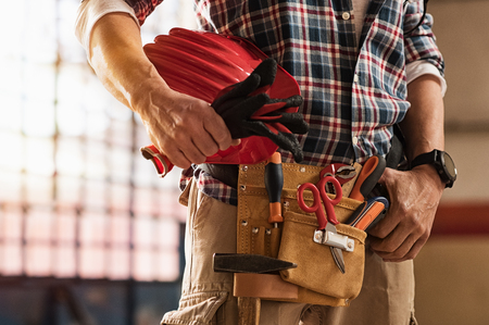 Foto de Closeup of bricklayer hands holding hardhat and construction equipment. Detail of mason man hands holding work gloves and wearing tool kit on waist. Handyman with tools belt and artisan equipment. - Imagen libre de derechos
