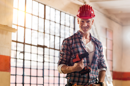 Photo pour Mature mason holding electric drill machine in a building site. Satisfied bricklayer with red hardhat looking at camera in a construction site. Portrait of mature workman with construction tool. - image libre de droit