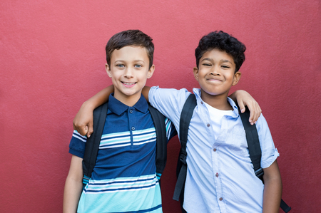 Photo pour Best children friends standing with hand on shoulder against red background. Happy smiling classmates standing together on red wall after school. Portrait of multiethnic schoolboys enjoying friendship. - image libre de droit