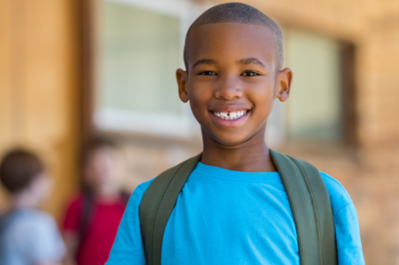 Foto de Smiling african american school boy with backpack looking at camera. Cheerful black kid wearing green backpack with a big smile. Elementary and primary school education. - Imagen libre de derechos