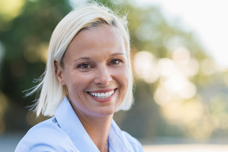 Foto de Portrait of mature woman smiling and looking at camera outdoor. Closeup face of a middle aged woman smiling at park. Blond mid woman relaxing in the lawn in a summer day. - Imagen libre de derechos