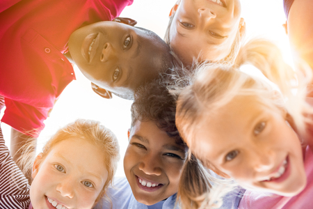 Photo pour Portrait of happy kids in circle looking down and embracing. Group of five multiethnic friends outdoor looking at camera and smiling. Closeup face of smiling children looking down at the camera together at park. - image libre de droit
