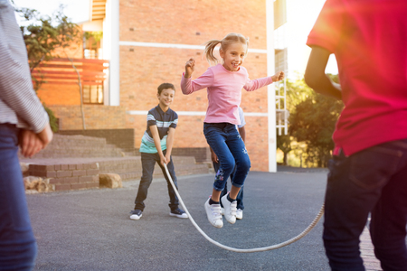 Photo pour Happy elementary kids playing together with jumping rope outdoor. Children playing skipping rope jumping game and laughing outdoors. Happy cute girl jumping over skipping rope held by her friends. - image libre de droit