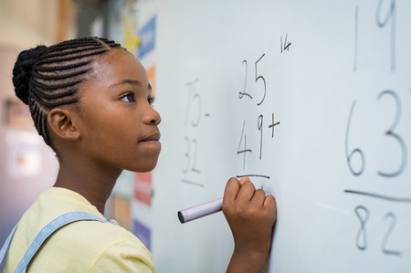 Photo pour Portrait of african girl writing solution of sums on white board at school. Black schoolgirl solving addition sum on white board with marker pen. School child thinking while doing mathematics problem. - image libre de droit