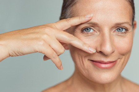 Foto de Portrait of smiling senior woman with perfect skin showing victory sign near eye on grey background.  Closeup face of mature woman showing successful results after anti-aging wrinkle treatment. Beauty mature skin care concept. - Imagen libre de derechos