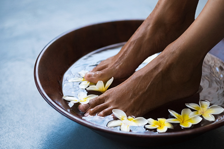 Foto de Woman soaking feet in bowl of water with floating frangipani flowers at spa. Closeup of a female feet at wellness center on pedicure procedure. Woman feet in spa wooden bowl with exotic white flowers. - Imagen libre de derechos