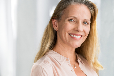 Foto de Portrait of mature woman enjoying life after retirement and looking at camera. Closeup face of happy senior woman with blond hair smiling. Beautiful smiling lady indoor. - Imagen libre de derechos