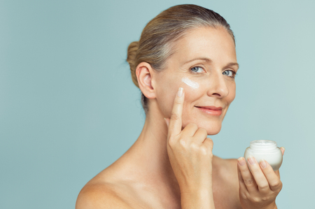 Photo pour Beautiful mature woman holding jar of skin cream for face and body isolated on grey background. Happy senior woman applying anti-aging moisturizer and looking at camera. Beauty and anti aging treatment. - image libre de droit