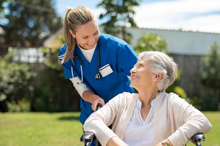 Foto de Nurse taking care of old woman in wheelchair outdoor. Friendly doctor caring about elderly disabled woman in wheelchair. Happy elderly woman with her caregiver at nursing home park. - Imagen libre de derechos