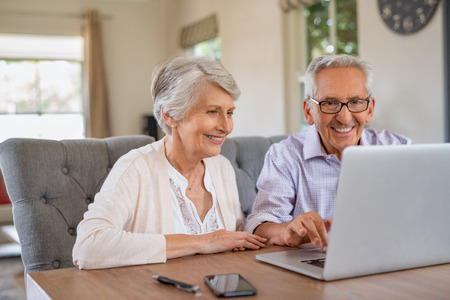 Photo pour Happy smiling retired couple using laptop at home. Cheerful elderly man and old woman using computer while sitting at table. Smiling pensioner showing woman notebook at home. - image libre de droit