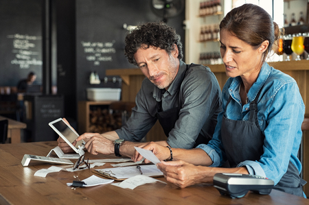 Photo for Man and woman sitting in cafeteria discussing finance for the month. Stressed couple looking at bills sitting in restaurant wearing uniform apron. Café staff sitting together looking at expenses and bills. - Royalty Free Image