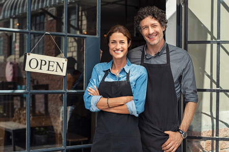 Foto de Two cheerful small business owners smiling and looking at camera while standing at entrance door. Happy mature man and mid woman at entrance of newly opened restaurant with open sign board. Smiling couple welcoming customers to small business shop. - Imagen libre de derechos