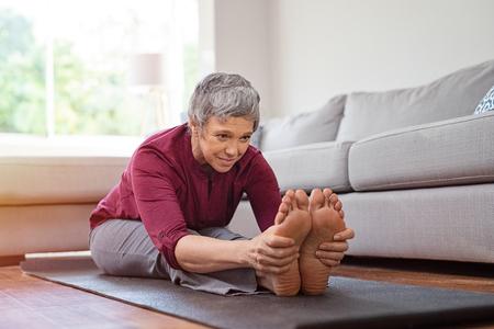Foto de Beautiful senior woman doing stretching exercise while sitting on yoga mat at home. - Imagen libre de derechos