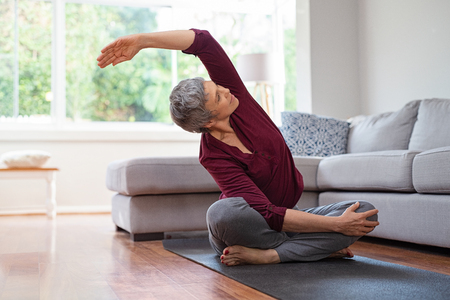 Foto de Senior woman exercising while sitting in lotus position. Active mature woman doing stretching exercise in living room at home. Fit lady stretching arms and back while sitting on yoga mat. - Imagen libre de derechos