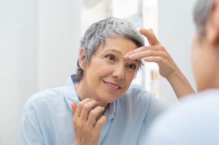 Foto de Mature woman looking her face and wrinkles in the bathroom mirror. - Imagen libre de derechos
