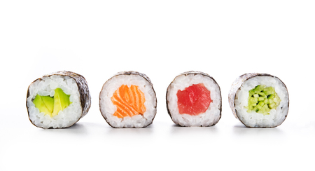 Foto de Four maki rolls in a row with salmon, avocado, tuna and cucumber isolated on white background. Fresh hosomaki pieces with rice and nori. Closeup of delicious japanese food with sushi roll. - Imagen libre de derechos