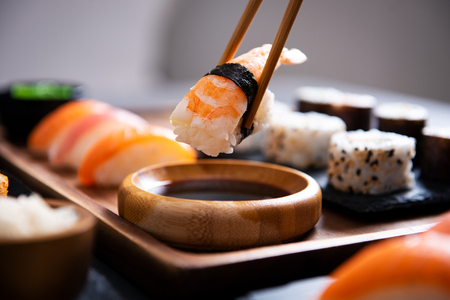 Foto de Closeup hand holding bamboo chopsticks with nigiri shrimp while soaking it in soy sauce. Detail of sushi set on wooden tray at restaurant while hand dip nigiri in soy sauce. Japanese cuisine concept. - Imagen libre de derechos