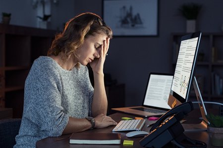 Foto de Mature and tired businesswoman working in the office until night. Portrait of a casual stressed lady with headache at desk near desktop computer. Exhausted business woman working late night at computer in office. - Imagen libre de derechos