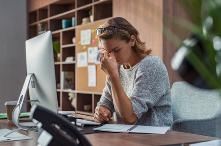 Photo for Exhausted businesswoman having a headache in modern office. Mature creative woman working at office desk with spectacles on head feeling tired. Stressed casual business woman feeling eye pain while overworking on desktop computer. - Royalty Free Image