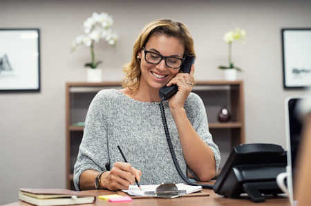 Photo pour Beautiful mature woman talking on phone at creative office. Happy smiling businesswoman answering telephone at office desk. Casual business woman sitting at her desk making telephone call and taking notes on notebook. - image libre de droit