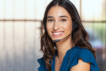 Foto de Customer support woman smiling and looking at camera. Portrait of happy customer support phone operator at call center wearing headset. Cheerful executive at your service working at office. - Imagen libre de derechos
