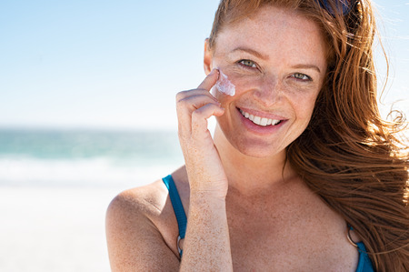 Photo pour Smiling young woman applying sunscreen lotion on face at beach, with copy space. Beautiful mature woman with red hair enjoying summer at sea. Portrait of happy girl using sunblock on her delicate skin with freckles and looking at camera. - image libre de droit
