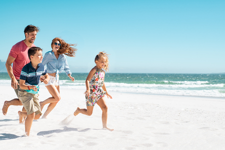 Foto de Cheerful young family running on the beach with copy space. Happy mother and smiling father with two children, son and daughter, having fun during summer holiday. Playful casual family enjoying playing at beach during vacaton. - Imagen libre de derechos