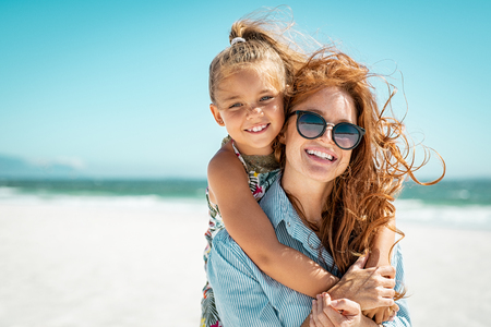 Photo pour Smiling mother and beautiful daughter having fun on the beach. Portrait of happy woman giving a piggyback ride to cute little girl with copy space. Portrait of happy blonde kid embracing her mom wearing spectacles at beach during summer vacation. - image libre de droit