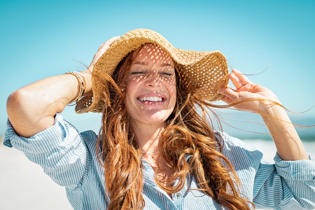 Photo pour Closeup face of mature woman wearing straw hat enjoying the sun at beach. Happy young woman smiling during summer vacation at sea. Portrait of beautiful lady relaxing at beach while holding large brim for the wind. - image libre de droit