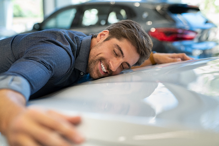 Foto de Happy young man hugging his new car in showroom. Satisfied guy with closed eyes embracing the hood of the automobile. Dreaming man lying on car bonnet hugging it. - Imagen libre de derechos