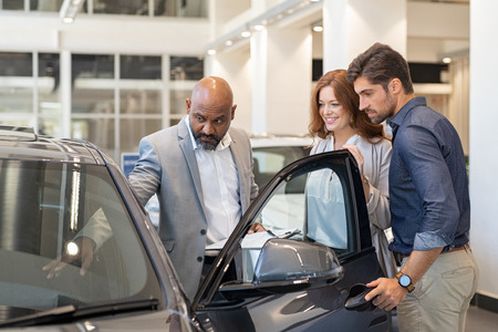 Photo pour Mature african salesman showing all the car features to young couple. Car dealer showing new car to young man and beautiful woman in showroom. Couple buying a new suv in a auto dealership. - image libre de droit