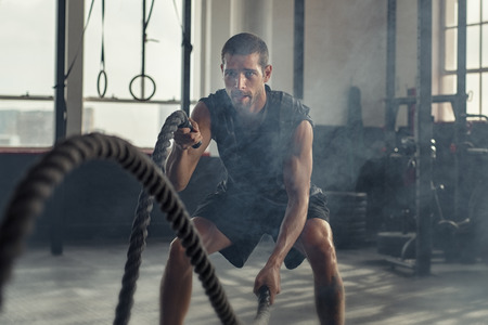 Foto de Strong young man working out with battle ropes in a crossfit gym. Muscular sportsman doing cross excursion with ropes in workout gym. Determined guy using battle rope while doing physical training. - Imagen libre de derechos