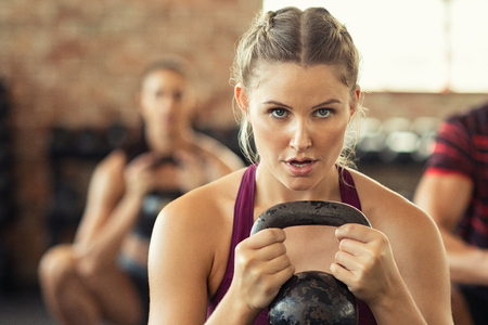 Foto de Portrait of concentrated young woman working out with kettlebell at crossfit gym. Closeup face of determined girl doing squat session while holding kettlebell and training biceps. Fitness class lifting heavy weights while squatting. - Imagen libre de derechos