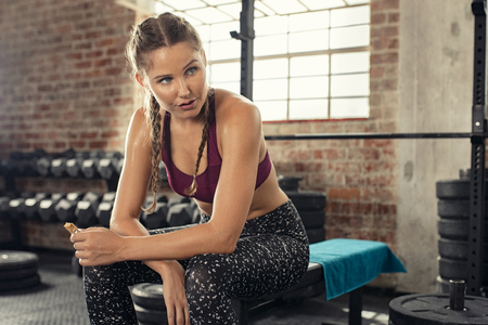 Foto de Sweaty young woman eating energy bar at gym after strong workout session. Beautiful exhausted woman enjoying chocolate bar after a heavy workout in fitness gym. Fit tired girl sitting and biting a snack while resting after training with copy space. - Imagen libre de derechos