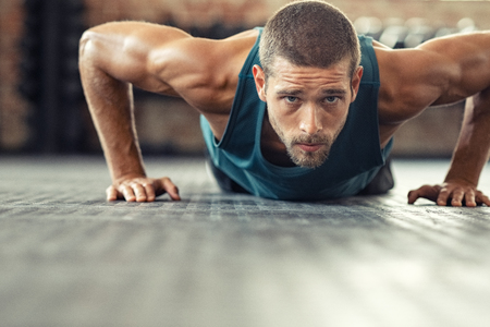 Foto de Young athlete doing push ups as part of bodybuilding training. Muscular guy doing a pushup on floor at crossfit gym. Determined athletic guy in sportswear exercising. - Imagen libre de derechos