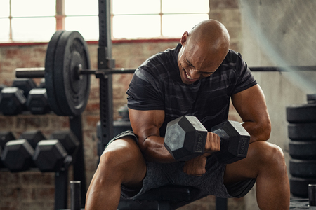 Foto de Muscular guy in sportswear lifting dumbbell while sitting on bench at crossfit gym. Mature african american athlete using dumbbell during a workout. Strong man under physical exertion pumping up bicep muscule with heavy weight. - Imagen libre de derechos