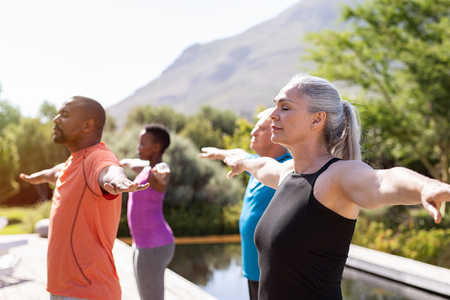 Photo pour Group of senior people with closed eyes stretching arms outdoor. Happy mature people doing breathing exercise near pool. Yoga class with women and men doing breath exercise with outstretched arms. Balance and meditation concept. - image libre de droit