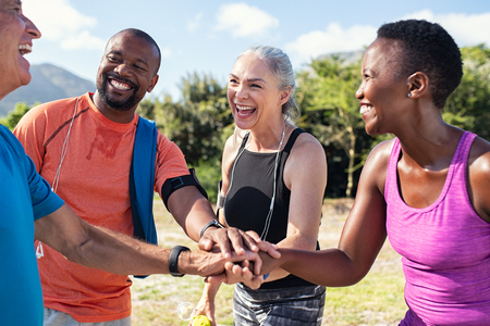 Photo for Laughing senior and multiethnic sports people putting hands together at park. Happy group of men and women smiling and stacking hands outdoor. Multiethnic sweaty team cheering after intense training. - Royalty Free Image